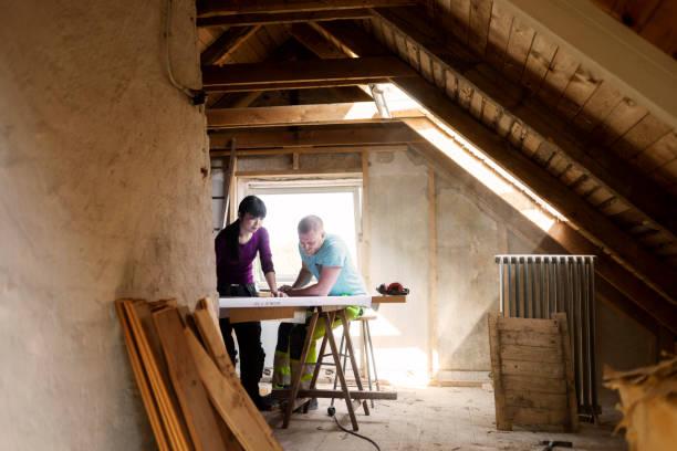 Couple qui fait des travaux pour aménager les combles de leur maison