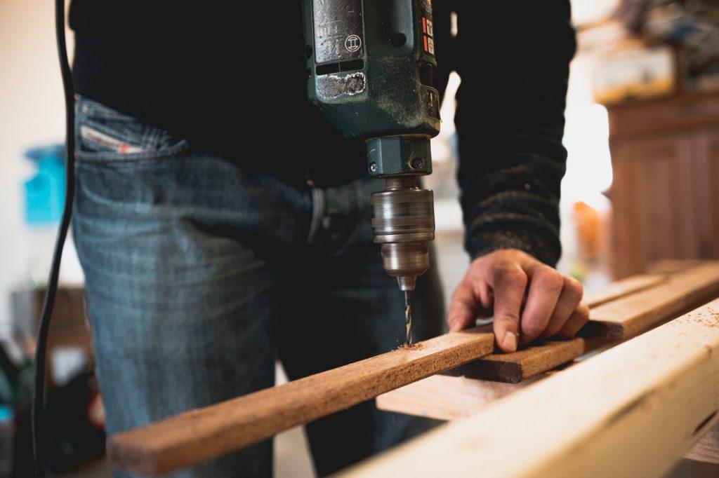 personne qui utilise une perceuse sur une planche de bois