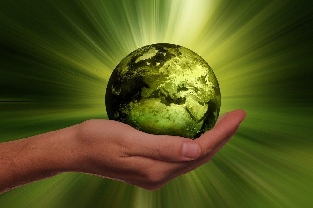 main qui tient une planète miniature de couleur verte